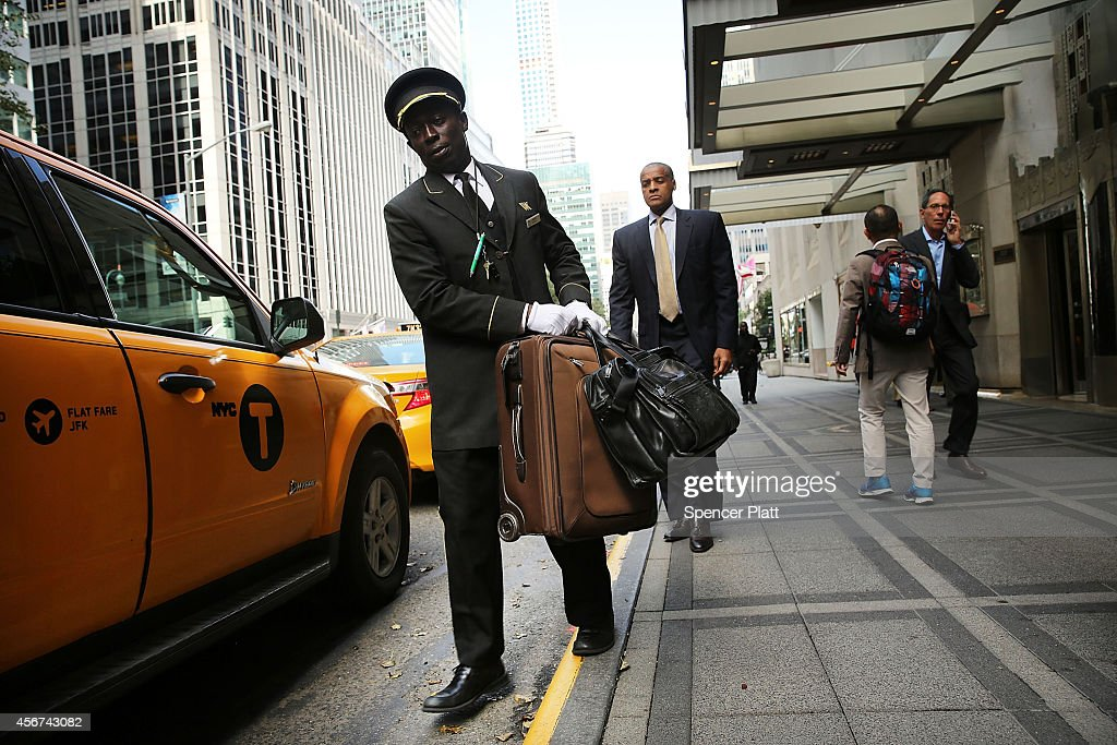 An employee helps a guest with his bags at the Waldorf Astoria the landmark New York hotel is viewed on October 6 2014 in New York City It was...