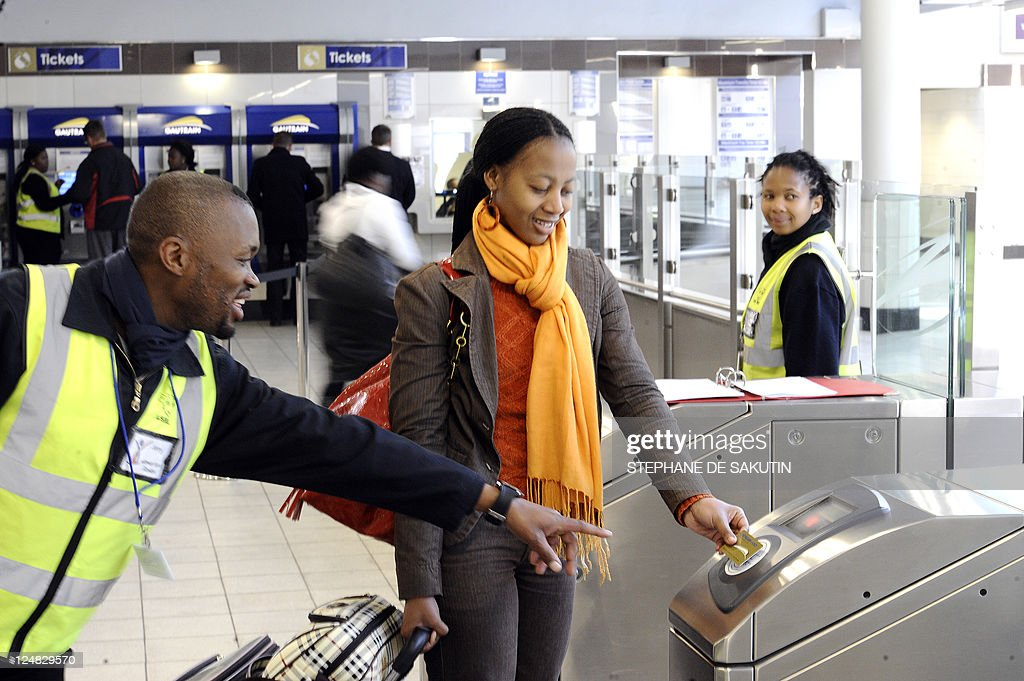 An employee helps a passenger to go through a turnstile on August 2 2011 at Sandton station in a Johannesburg suburb to ride the Gautrain Africa's...