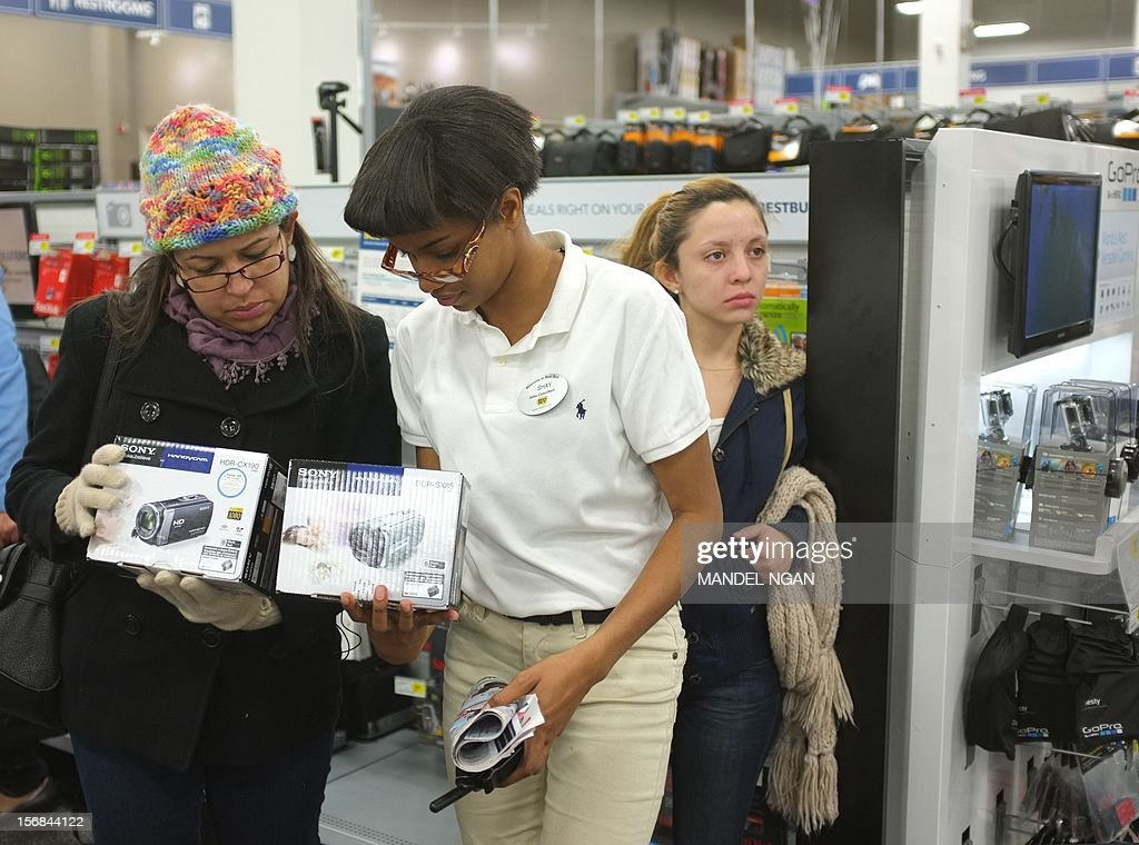 An employee helps a shopper inside of a Best Buy store during their Black Friday sale which started at midnight on November 23, 2012 in Rockville, Maryland. Thanksgiving, the last US holiday undisturbed by mass commercialization, is now victim to the ever advancing Christmas shopping season, with stores welcoming shopaholics before the family turkey can be taken from the oven.