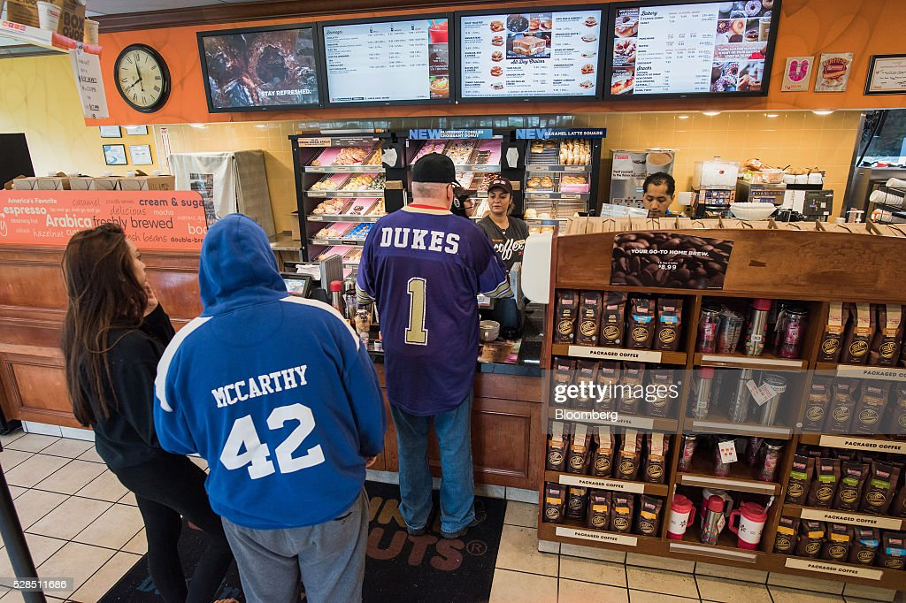 An employee helps customers at a Dunkin' Donuts Inc. location in Ramsey, New Jersey, U.S., on Thursday, May 5, 2016. Dunkin' Brands Group Inc., a leading franchiser in the quick service restaurants (QSR) sector, operates in almost 60 countries around the world with more than 11,300 Dunkin' Donuts restaurants and 7,500 Baskin-Robbins locations. Photographer: Ron Antonelli/Bloomberg via Getty Images
