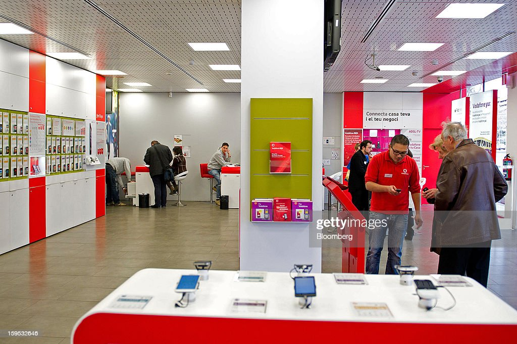 An employee helps customers, right, select mobile phones inside a Vodafone Group Plc store in Barcelona, Spain, on Tuesday, Jan. 15, 2013. Vodafone Group Plc, the world's second largest mobile-phone company, plans to reduce the workforce at its Spanish unit as unemployment exceeding 25 percent in the recession-plagued country causes sales to drop. Photographer: David Ramos/Bloomberg via Getty Images