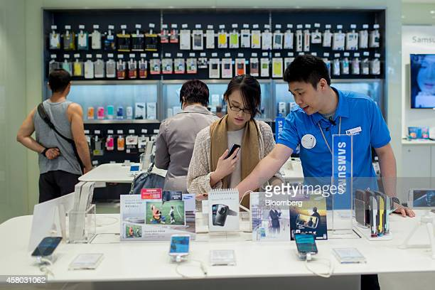 An employee helps with a customer browsing Samsung Electronics Co smartphones at a Samsung Partnershop retail store in the Central district of Hong...