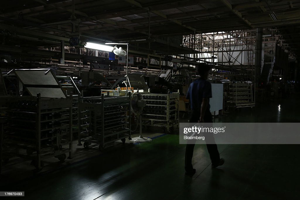 An employee holding a bottle of water walks past the halted assembly line at the Hyundai Motor Co. plant during a strike by the company's labor union in Ulsan, South Korea, on Tuesday, Aug. 20, 2013. Union members at Hyundai Motor, South Korea's largest automaker, staged a partial strike today that will continue tomorrow as they demand higher wages amid increasing competition with Japanese carmakers. Photographer: SeongJoon Cho/Bloomberg via Getty Images