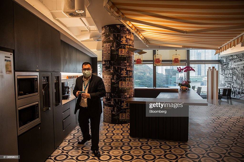An employee holding a cup walks through a pantry at the Microsoft Corp. Office and Experience Center during a media event for the opening of the workspace in Hong Kong, China, on Friday, March 4, 2016. Microsoft is rolling out a new service for its Windows 10 operating system to help large businesses detect hackers, security threats and unusual behavior on their networks, rivaling companies like FireEye Inc. and Symantec Corp. Photographer: Billy H.C. Kwok/Bloomberg via Getty Images