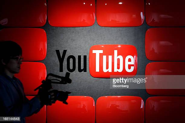 An employee holding recording equipment walks past Google Inc's YouTube logo displayed at the company's YouTube Space studio in Tokyo Japan on...