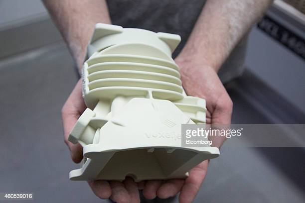 An employee holds a 2stroke automobile engine during manufacture at the Voxeljet AG 3D printing plant in Friedberg Germany on Monday Dec 15 2014...