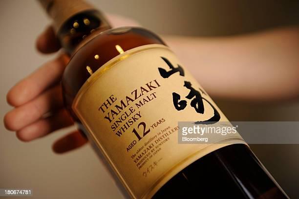 An employee holds a bottle of Suntory Holdings Ltd's Yamazaki whisky at the company's Yamazaki distillery in Shimamoto Osaka Japan on Friday Sept 13...
