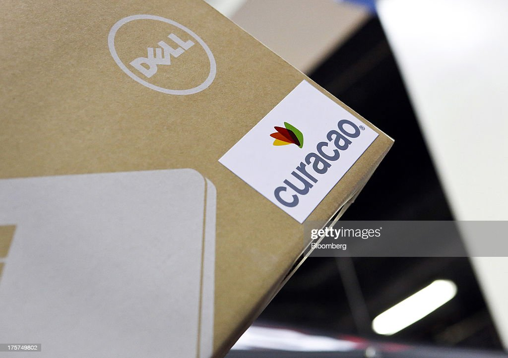 An employee holds a boxed Dell Inc. Inspiron 15 laptop during a give away at an event at a Curacao Department store in Los Angeles, California, U.S., on Wednesday, August 7, 2013. The Inspiron 15, an affordable notebook with an impressive battery life, is the only Spanish-language laptop manufactured and sold in the U.S. offered by Dell. Photographer: Patrick T. Fallon/Bloomberg via Getty Images