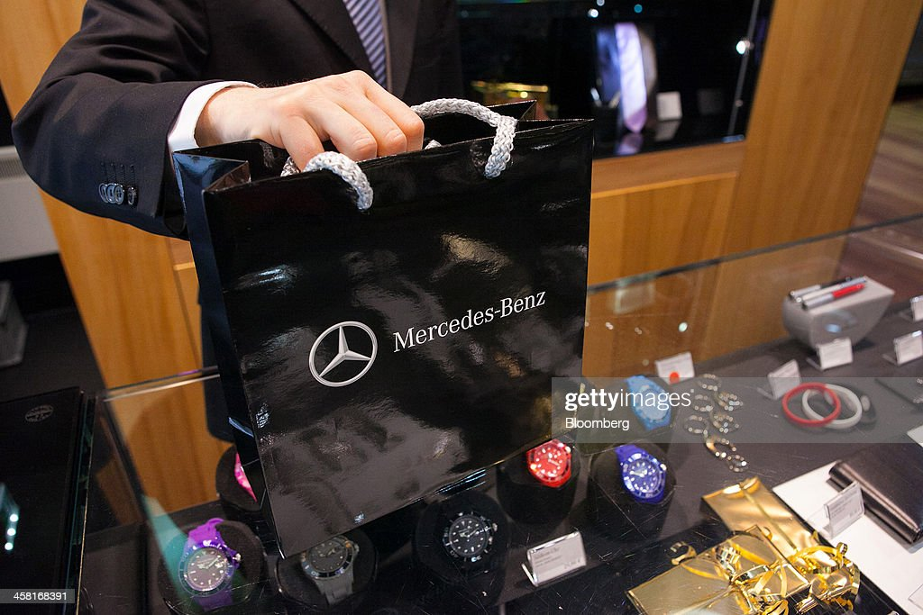 An employee holds a branded gift bag on a store counter in this arranged photograph inside the Mercedes-Benz Gallery showroom in Berlin, Germany, on Thursday, Dec. 19, 2013. European new-car sales rose a third consecutive month in November, the longest period of gains in four years. Photographer: Krisztian Bocsi/Bloomberg via Getty Images