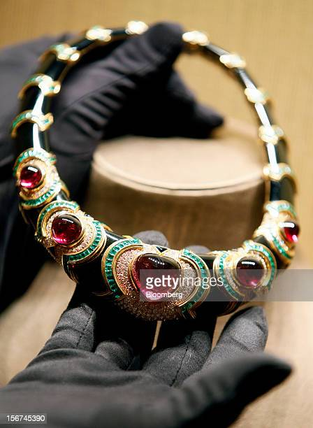 An employee holds a Bulgari Heritage Collection necklace in gold red tourmaline emerald onyx and diamond in this arranged photograph inside Bulgari...