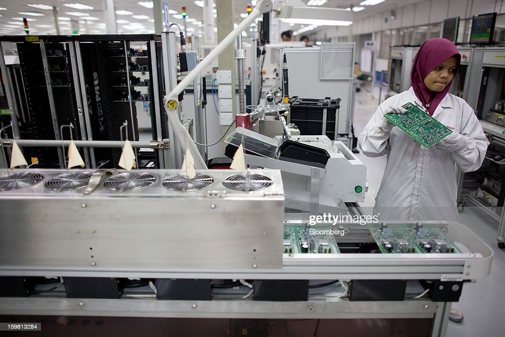 An employee holds a circuit board for the Jaguar Dual View Infotainment Control Module (ICM), produced by Robert Bosch GmbH for Jaguar Land Rover Plc, on the production line at the Robert Bosch plant in the Bayan Lepas Industrial Zone on Penang Island, Malaysia, on Thursday, Jan. 17, 2013. Robert Bosch GmbH is the world's largest automotive supplier. Photographer: Lam Yik Fei/Bloomberg via Getty Images