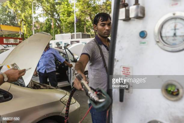 An employee holds a compressed natural gas nozzle at an Indraprastha Gas Ltd gas station in New Delhi India on Wednesday May 17 2017 Indraprastha...