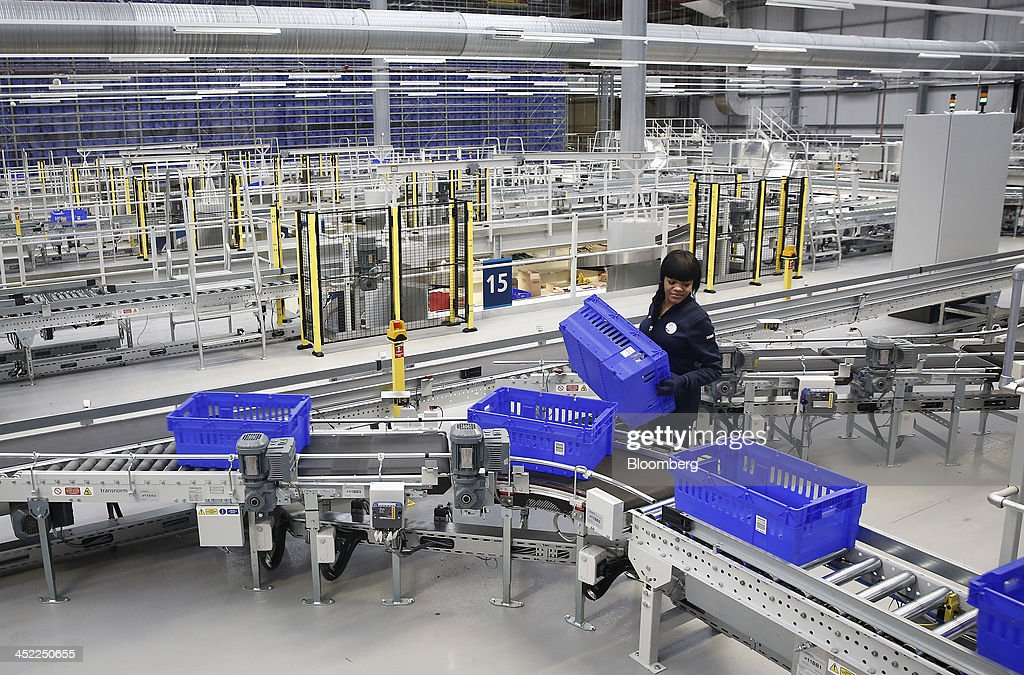 An employee holds a crate beside a conveyor belt at a Tesco Plc on-line distribution center, in Erith, U.K., on Wednesday, Nov. 27, 2013. Tesco Plc, the U.K.'s largest retailer, will sell land near some of its Polish hypermarkets to attract additional services around those stores. Photographer: Simon Dawson/Bloomberg via Getty Images
