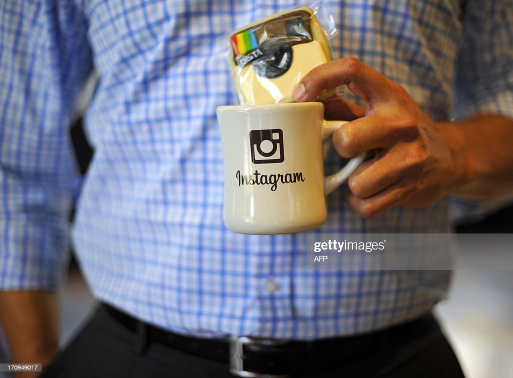 An employee holds a cup with the Instagram logo at Facebook's corporate headquarters during a media event in Menlo Park, California, on June 20, 2013. Facebook announced Thursday that it will add smartphone video-sharing to its Instagram photo-based social network, in a move that challenges Twitter's popular Vine service. Instagram video apps tailored for iPhones and smartphones powered by Google-backed Android software feature 13 filters for special effects and post to people's Facebook pages the same way pictures do, according to Systrom. AFP PHOTO Josh Edelson