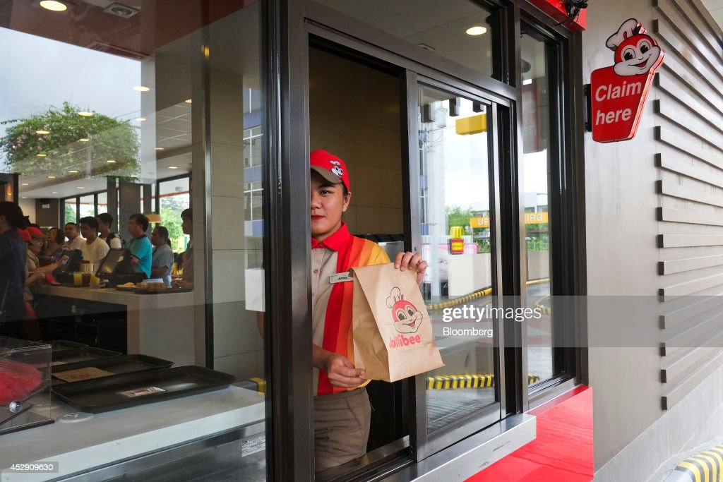 An employee holds a customer's order ready for collection in the drive-through section of a Jollibee Foods Corp. restaurant in Quezon City, Metro Manila, the Philippines, on Monday, July 28, 2014. Jollibee, which outsells McDonald's Corp. in the Philippines, plans to double earnings in five years as it accelerates its expansion in China and seeks an acquisition in the U.S. Photographer: Veejay Villafranca/Bloomberg via Getty Images