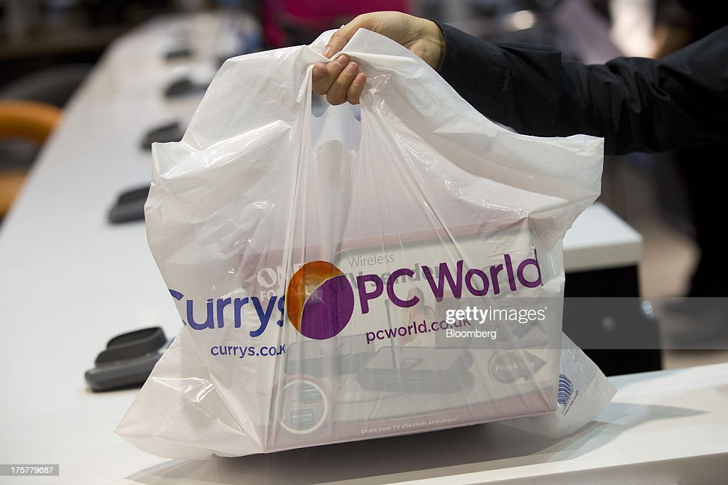 An employee holds a customer's purchase in a branded carrier bag in this arranged photograph taken inside a Currys and PC World 2 in 1 store, operated by Dixons Retail Plc, at the Westfield Stratford City retail complex in London, U.K., on Thursday, Aug. 8, 2013. U.K. consumer confidence rose to the highest in more than three years as Britons' optimism about the economic outlook improved. Photographer: Simon Dawson/Bloomberg via Getty Images
