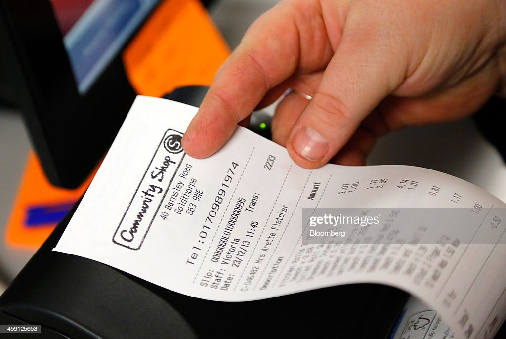 An employee holds a customer's receipt in this arranged photograph inside the Community shop, a supermarket for low-income families, in Goldthorpe, U.K., on Monday, Dec. 23, 2013. Company Shop Ltd. created the Community shop for people in, or bordering on, food poverty, selling surplus goods from major retailers at discounted prices. Photographer: Paul Thomas/Bloomberg via Getty Images