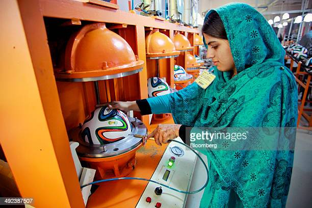An employee holds a hose inserted into the valve of an Adidas AG 'Brazuca' soccer ball in a thermobonding molding machine on the production line at...