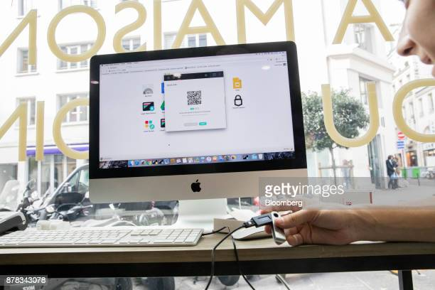 An employee holds a ledger wallet smartcard device as a Quick Response code is displayed on a Apple Inc computer monitor during an ethereum currency...