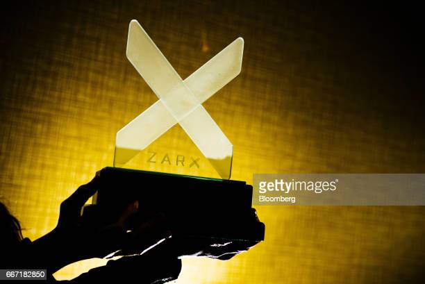 An employee holds a logo in this arranged photo taken at the ZAR X South Africa's second stock exchange in Johannesburg South Africa on Tuesday April...