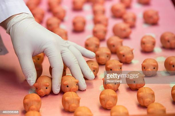 An employee holds a marzipan piglet during the handpainting process inside the factory of traditional confectionary maker JG Niederegger GmbH in...