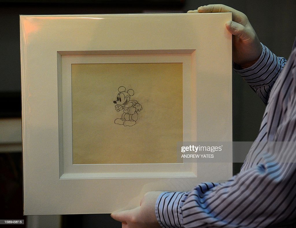 An employee holds a never-before-seen original artwork pencil drawing of Micky Mouse from 1933 at the Tatton Park fine arts and antiques fair at Tatton Park in Knutsford, north-west England, on January 4, 2013. The drawing is from the collection of a well-known storyboard artist from the 1930s and 40s and is on sale.