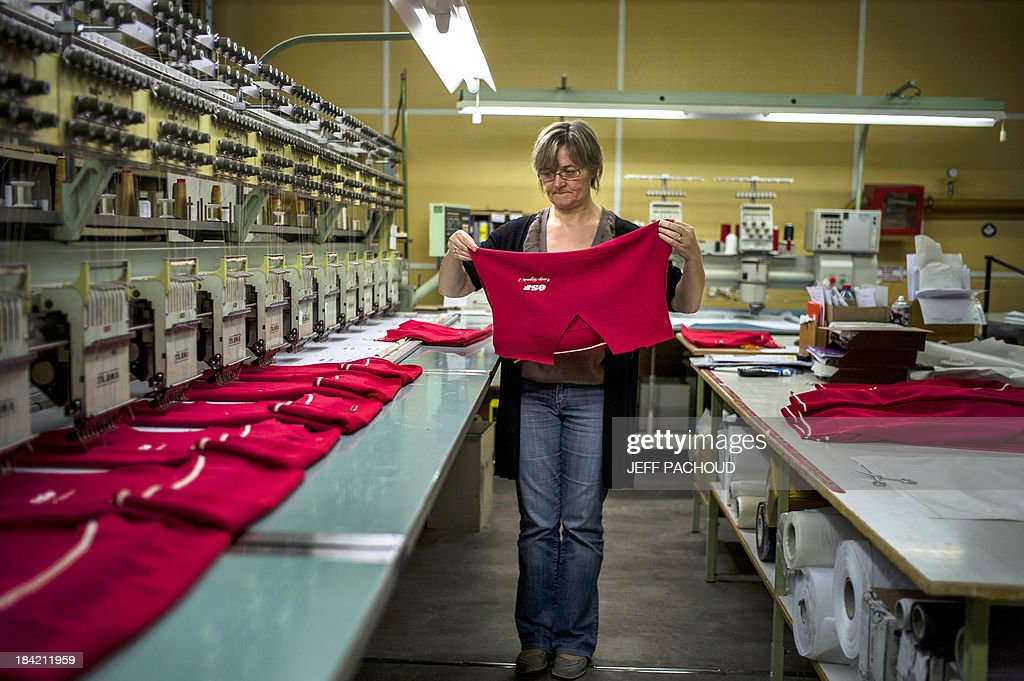 An employee holds a new French Ski School (ESF) red sweater on October 11, 2013 in a Degre 7 knitting workshop based in Le Creusot, eastern France. The brand will produce the popular red sweaters worn by ESF instructors, reconnecting the product with the 'Made in France' label.