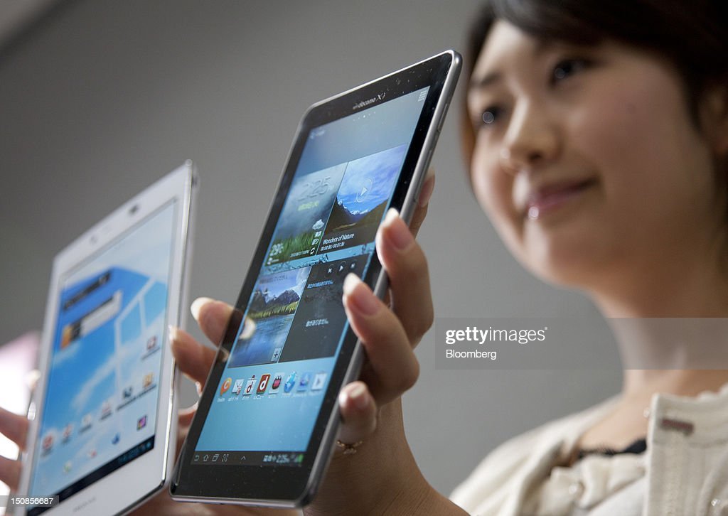 An employee holds a NTT DoCoMo Inc. Galaxy Tab 7.7 Plus SC-01E tablet computer, manufactured by Samsung Electronics Co., right, and a Medias Tab UL N-08D tablet computer, by NEC Casio Mobile Communications Ltd., during a product launch in Tokyo, Japan, on Tuesday, Aug. 28, 2012. NTT DoCoMo Inc., Japan's biggest mobile-phone company, released their latest tablet and smartphone series today. Photographer: Tomohiro Ohsumi/Bloomberg via Getty Images