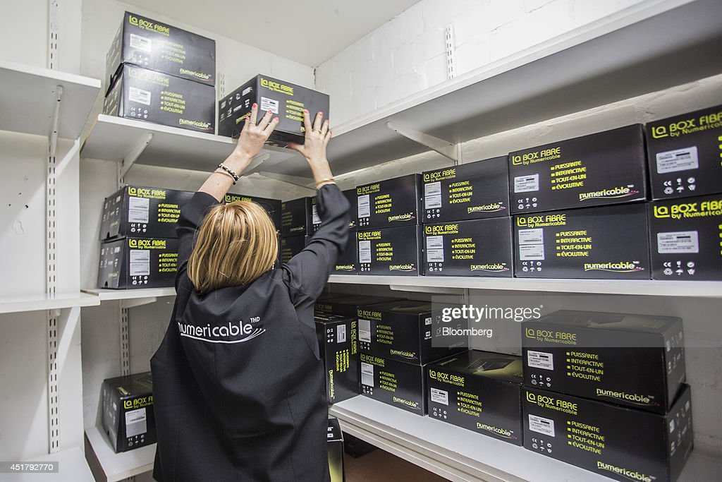 An employee holds a packaged La Box Fibre multimedia set top box in a storage room inside a Numericable Group SA cable-television and internet store, operated by Altice SA, in Bordeaux, France, on Friday, July 4, 2014. Altice is raising its stake in Numericable after agreeing in April to merge the French cable provider with Vivendi SA's phone unit SFR, a transaction valued at more than 17 billion euros. Photographer: Balint Porneczi/Bloomberg via Getty Images