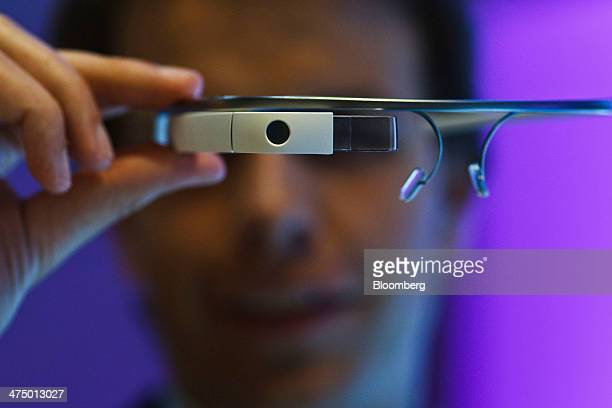 An employee holds a pair of Google Glass connected glasses on day three of the Mobile World Congress in Barcelona Spain on Wednesday Feb 26 2014 Top...