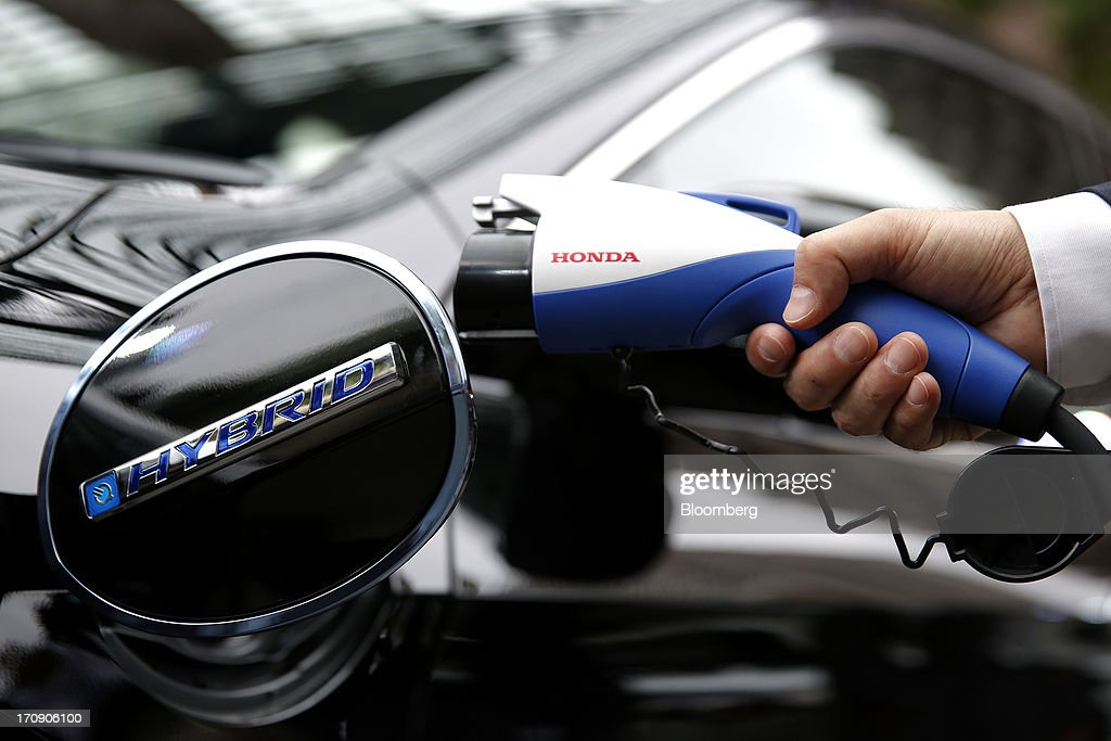 An employee holds a plug-in charger for Honda Motor Co.'s Accord plug-in hybrid sedan for a photograph at its unveiling in Tokyo, Japan, on Thursday, June 20, 2013. Honda, Japan's third-largest carmaker, unveiled a hybrid sedan at a 20 percent higher price than Toyota Motor Corp.'s gasoline-electric Camry, betting drivers will pay extra for fuel economy. Photographer: Kiyoshi Ota/Bloomberg via Getty Images