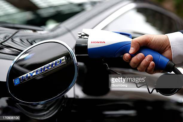 An employee holds a plugin charger for Honda Motor Co's Accord plugin hybrid sedan for a photograph at its unveiling in Tokyo Japan on Thursday June...