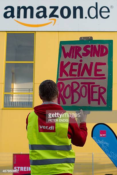 An employee holds a poster reading 'we are no robot' outside a centre of US online retail giant Amazon in Leipzig eastern Germany on October 27 2014...