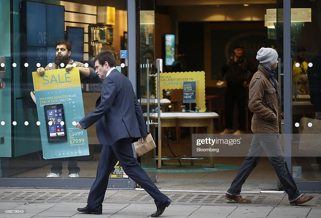 An employee holds a sale poster in the window of an EE mobile phone store as pedestrians pass in London, U.K., on Tuesday, Dec. 24, 2013. Vodafone Group Plc; EE, which is co-owned by Orange SA and Deutsche Telekom AG; Three, owned by Hutchison Whampoa Ltd.; and Virgin Media Inc. said they will cap bills run up on phones reported lost or stolen, stop mid-contract price increases, and support the U.K. government in its attempt to end roaming charges within the European Union. Photographer: Simon Dawson/Bloomberg via Getty Images