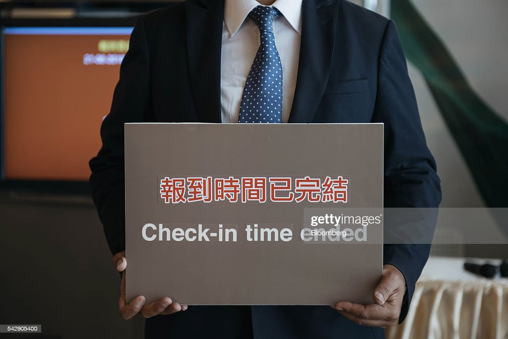 An employee holds a sign reading 'Check-In Time Ended' outside the sales office of Park Yoho Venezia, a residential property developed by Sun Hung Kai Properties Ltd., in Hong Kong, China, on Saturday, June 25, 2016. Sun Hung Kai, Hong Kong's largest developer by market value, is offering mortgages worth as much as 120 percent of a home's value at one of its projects as sales have slumped in the city. Photographer: Anthony Kwan/Bloomberg via Getty Images