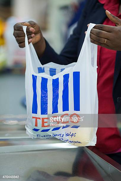 An employee holds a Tescobranded plastic shopping bag as she works at a checkout desk inside a Tesco supermarket operated by Tesco Plc in London UK...