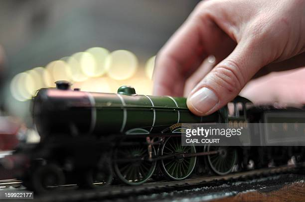 An employee holds a toy train on the Hornby stand during the London Toy Fair in Olympia central London on January 23 2013 AFP PHOTO / CARL COURT