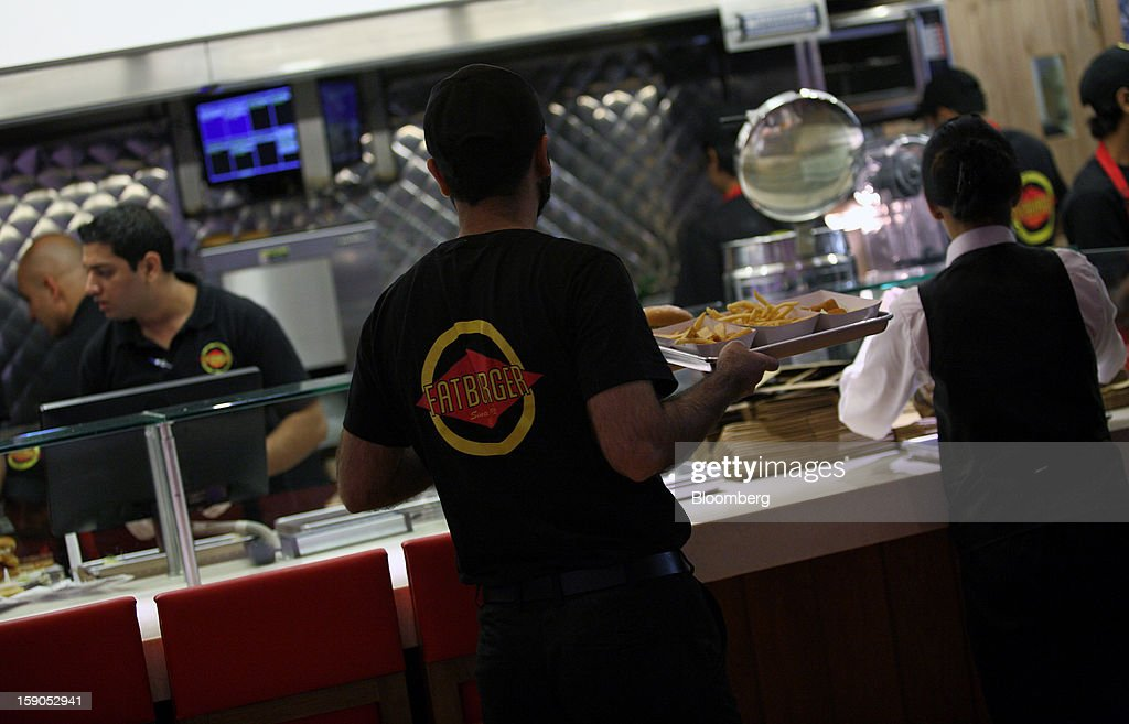 An employee holds a tray of food at a Fatburger outlet in Karachi, Pakistan, on Saturday, Jan. 5, 2013. Fatburger opened its first outlet in Pakistan to the public on Jan. 5. Photographer: Asim Hafeez/Bloomberg via Getty Images