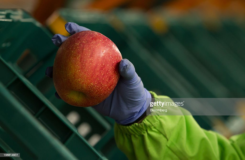 An employee holds an apple at the E-Mart Co. Fresh Center, a sorting facility, in Icheon, South Korea, on Wednesday, Nov. 21, 2012. South Korea's household debt rose to a record in the third quarter as borrowing increased to finance homes and consumption. Photographer: SeongJoon Cho/Bloomberg via Getty Images