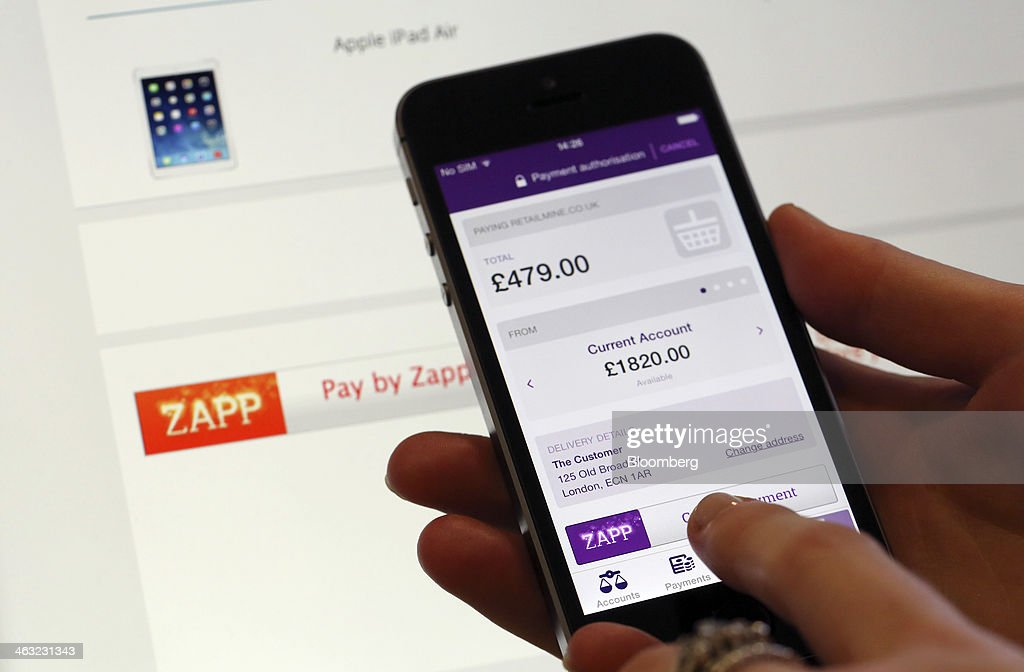 An employee holds an Apple Inc. iPhone with a demonstration bank payment web page using the Zapp money transfer and payment system in this arranged photograph at the company's offices in London, U.K., on Thursday, Jan. 16, 2014. Zapp, a unit of Vocalink Ltd., has created a system that will allow customers of major banking institutions to see their balance and pay for goods in real-time. Photographer: Chris Ratcliffe/Bloomberg via Getty Images