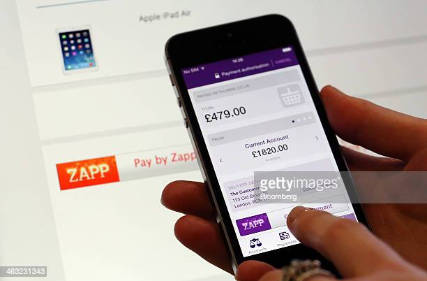 An employee holds an Apple Inc iPhone with a demonstration bank payment web page using the Zapp money transfer and payment system in this arranged...