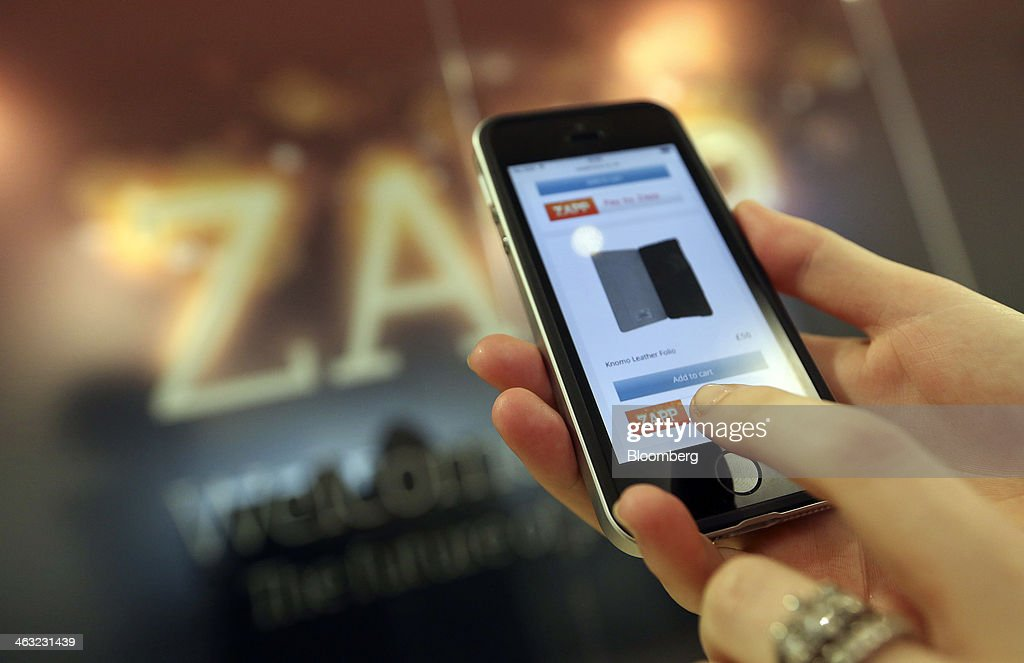 An employee holds an Apple Inc. iPhone with the 'check out' section of a demonstration bank payment web page using the Zapp money transfer and payment system in this arranged photograph at the company's offices in London, U.K., on Thursday, Jan. 16, 2014. Zapp, a unit of Vocalink Ltd., has created a system that will allow customers of major banking institutions to see their balance and pay for goods in real-time. Photographer: Chris Ratcliffe/Bloomberg via Getty Images