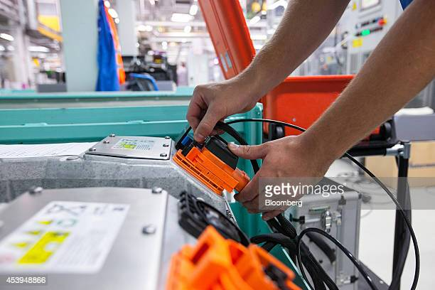 An employee holds an electrical power plug during final testing of lithiumion batteries at the Bayerische Motoren Werke AG automobile manufacturing...