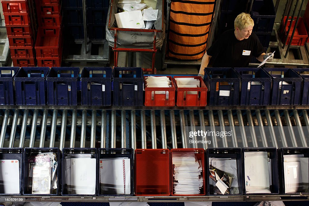 An employee holds an envelope as crates of mail move along a conveyor belt at the PostNL NV mail sorting center in Nieuwegein, Netherlands, on Friday, Sept. 27, 2013. PostNL NV rose the most in two months on Sept. 19 after the Dutch postal operator raised its full-year forecast and announced higher prices for stamps. Photographer: Jasper Juinen/Bloomberg via Getty Images