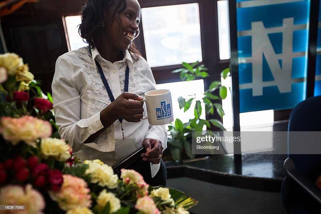 An employee holds an NSE-branded mug inside the Nairobi Stock Exchange (NSE) in Nairobi, Kenya, on Friday, March 1, 2013. Next week's presidential vote will be the first since disputed elections in 2007 triggered ethnic fighting in which more than 1,100 people died and another 350,000 fled their homes. Photographer: Trevor Snapp/Bloomberg via Getty Images
