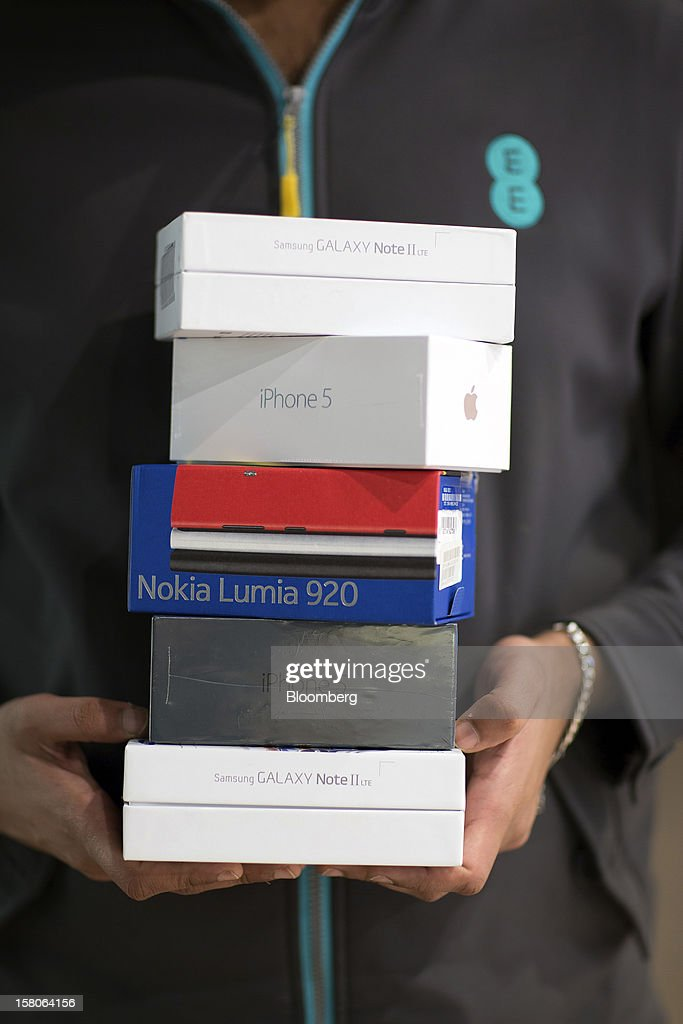 An employee holds boxes of 4G-ready handsets manufactured by Apple Inc., Samsung Electronics Co., and Nokia Oyj, in this arranged photograph inside a EE (Everything Everywhere) store, a joint venture between France Telecom SA and Deutsche Telekom AG, in Stratford, U.K., on Monday, Dec. 5, 2012. France Telecom CEO Stephane Richard said in an interview last month that the Paris-based company has received interest from private-equity firms seeking a minority stake in the 50-50 venture, and may also consider an initial public offering of the unit. Photographer: Jason Alden/Bloomberg via Getty Images