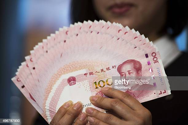 An employee holds Chinese onehundred yuan banknotes in an arranged photograph at the Bank of China Hong Kong Ltd headquarters in Hong Kong China on...