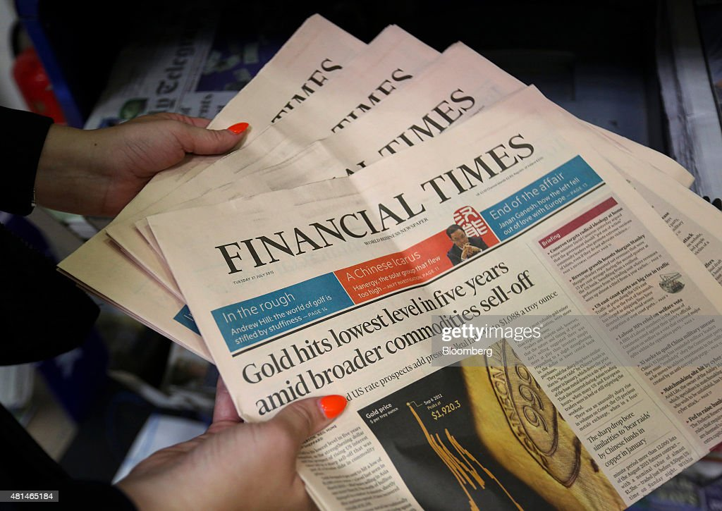 An employee holds copies Financial Times newspapers in this arranged photograph at a newsagent store in Danbury Essex UK on Tuesday July 2015 Pearson...
