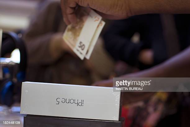 An employee holds euro banknotes beside an Apple's new iPhone 5 smartphone at a cash register in an Apple store on September 21 2012 in Paris The...