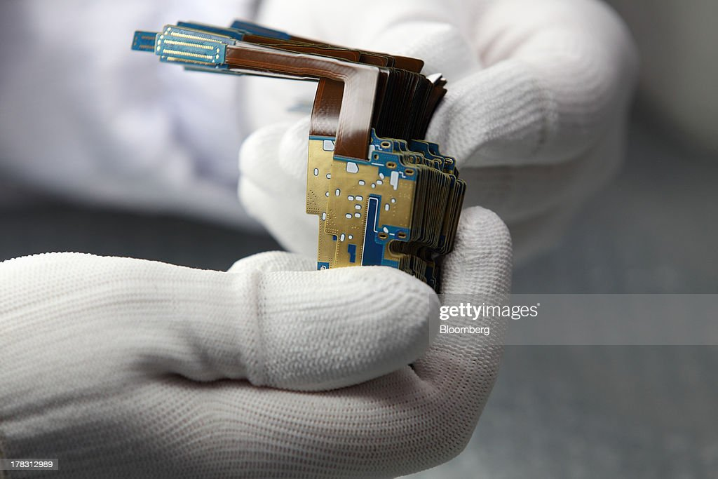 An employee holds Flexible Printed Circuit Boards (F-PCB) on the production line at the Seil Electronics Co. factory in Incheon, South Korea, on Wednesday, Aug. 28, 2013. South Korea has surpassed Brazil, Russia and India to become the second-biggest emerging stock market for the first time since 2006, as a stable won and record current-account surplus lure investors. Photographer: SeongJoon Cho/Bloomberg via Getty Images
